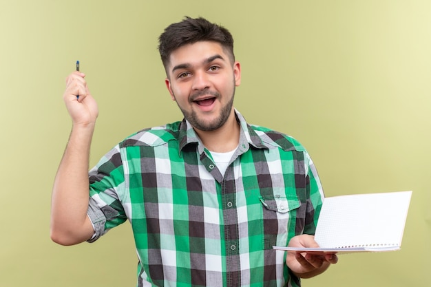 Young handsome guy wearing checkered shirt happily found the solution of problem holding pen and copybook standing over khaki wall Free Photo