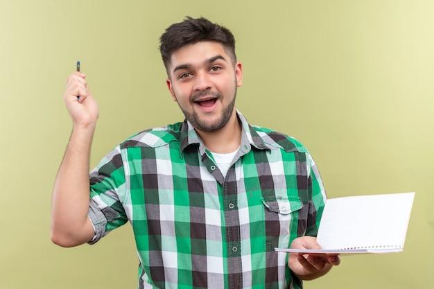 Молодой красивый парень в клетчатой рубашке с радостью нашел решение проблемы, держа ручку и тетрадь над стеной цвета хаки Бесплатные Фотографии