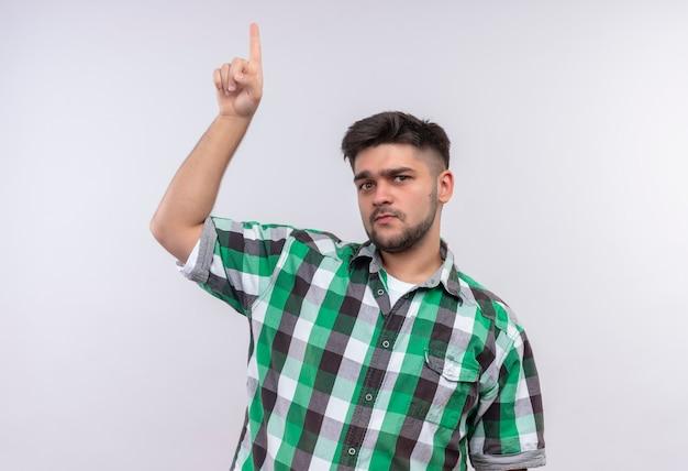 Молодой красивый парень в клетчатой рубашке смотрит вверх с указательным пальцем, стоящим над белой стеной Бесплатные Фотографии