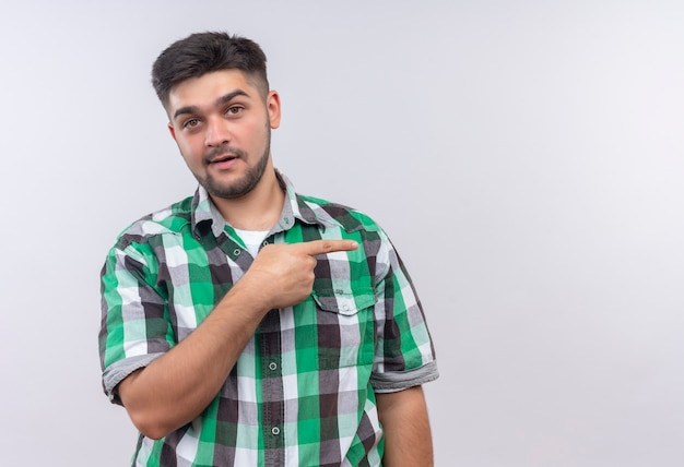 Молодой красивый парень в клетчатой рубашке удивленно смотрит влево, указывая указательным пальцем правой руки над белой стеной Бесплатные Фотографии