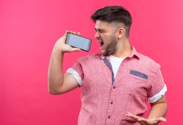 Молодой красивый парень в розовой рубашке поло поет по телефону, стоя над розовой стеной Бесплатные Фотографии