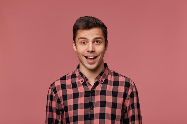 체크 무늬 셔츠에 젊은 잘 생긴 행복 놀란 남자, 놀란 표정으로 카메라를 바라보고, Iso; 활짝 열려 입으로 분홍색 배경 위에 Ated. 무료 사진