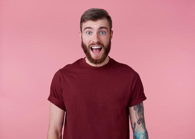 Giovane uomo barbuto rosso stupito felice bello in maglietta rossa, si leva in piedi su sfondo rosa guarda la telecamera con la bocca spalancata e gli occhi. Foto Gratuite