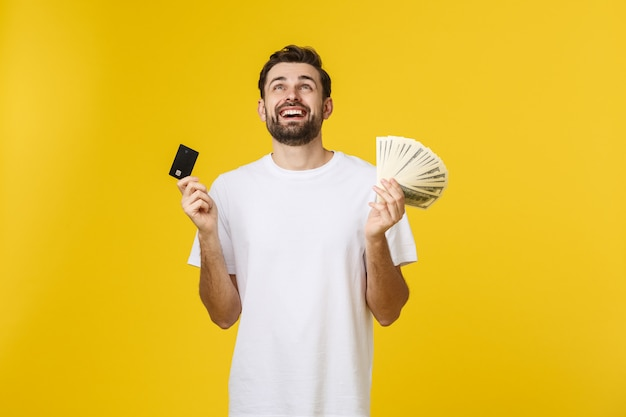 Young handsome happy smiling man holding banking card and cash in his hands isolated on yellow. Premium Photo