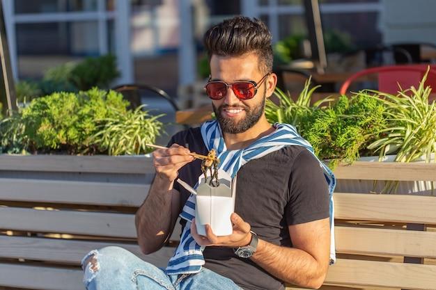 Молодой красивый хипстерский парень ест китайскую лапшу из ланч-бокса, сидя на скамейке в парке в солнечный летний день. концепция здорового и сытного перекуса. Premium Фотографии