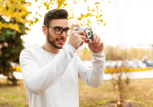 Young handsome hipster guy walks in a beautiful autumn park Premium Photo