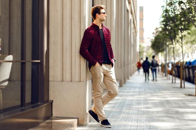 Молодой красивый хипстерский мужчина позирует на европейской улице, солнечные теплые тоновые цвета, повседневная модная одежда, путешествующее настроение. Бесплатные Фотографии