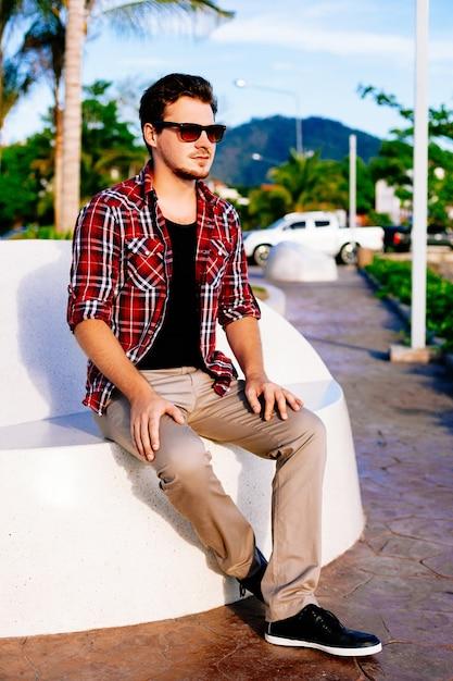 島の公園で晴れた日にリラックスした若いハンサムな流行に敏感な男 無料写真