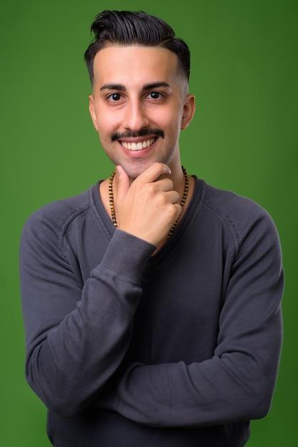 緑の口ひげを持つ若いハンサムなイラン人 Premium写真