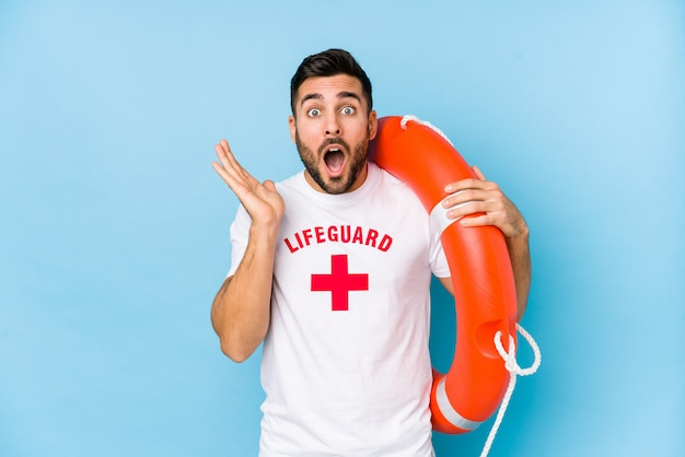 Young handsome lifeguard man isoalted surprised and shocked. Premium Photo