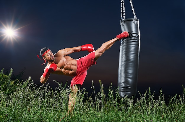 Young handsome male boxer practicing skills at night Premium Photo