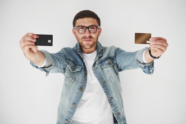 Молодой красивый мужской руководитель бизнеса в повседневной одежде держит кредитную карту в карманах на белом Бесплатные Фотографии