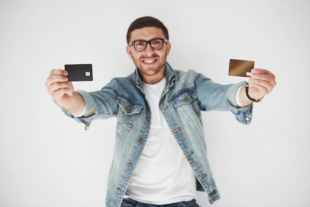 白のポケットにクレジットカードを保持しているカジュアルな服装で若いハンサムな男性ビジネスエグゼクティブ 無料写真