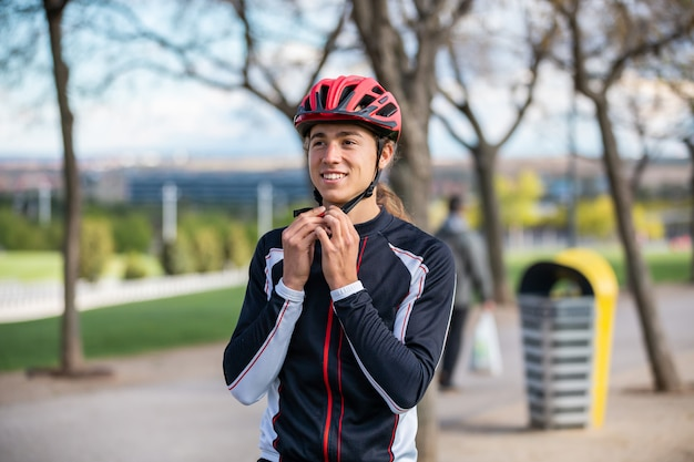 Young handsome male cyclist in sportswear buckling protective helmet in beautiful city park Premium Photo