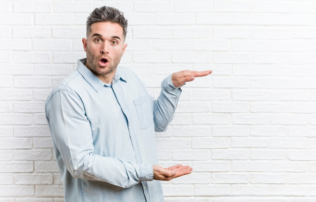 Young handsome man against a bricks wall shocked and amazed holding a copyspace between hands. Premium Photo