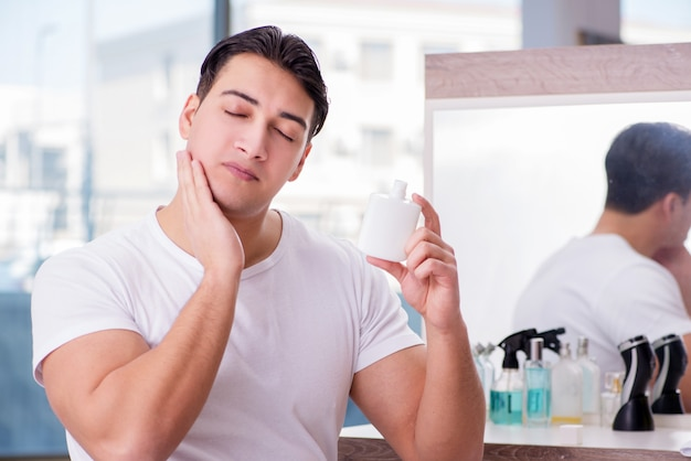 Young handsome man applying face cream Premium Photo