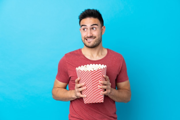 Young handsome man over blue holding a big bucket of popcorns Premium Photo