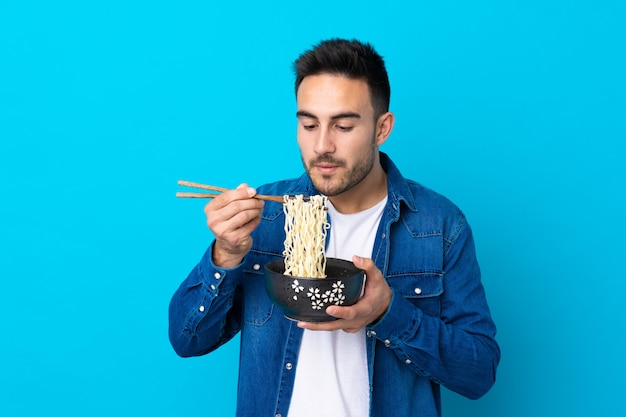Young handsome man over blue holding a bowl of noodles with chopstick Premium Photo