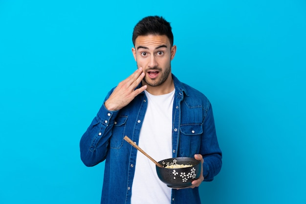 Young handsome man over blue holding a bowl of noodles with chopsticks and surprised Premium Photo