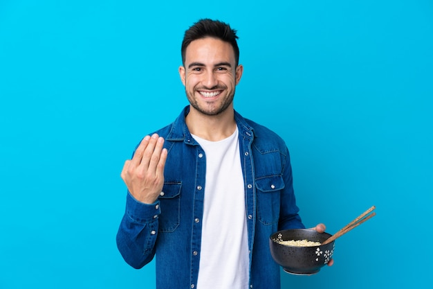 Young handsome man over blue inviting to come with hand. Premium Photo