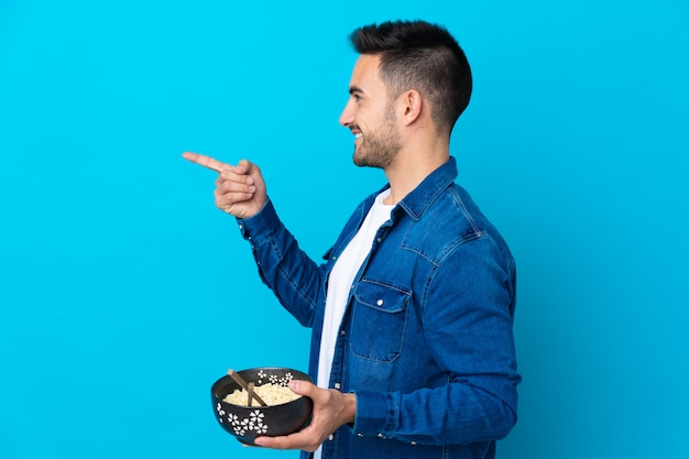 Young handsome man over blue pointing to the side to present a product Premium Photo