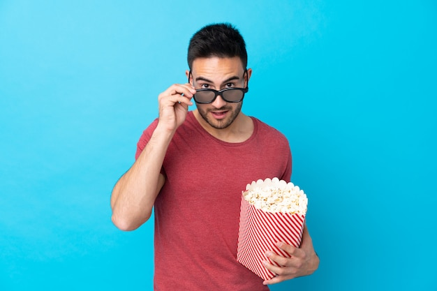 Young handsome man over blue surprised with 3d glasses and holding a big bucket of popcorns Premium Photo