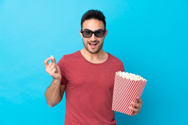 Young handsome man over blue with 3d glasses and holding a big bucket of popcorns Premium Photo