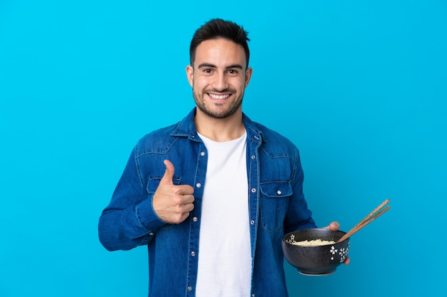 Young handsome man over blue with thumbs up because something good has happened Premium Photo