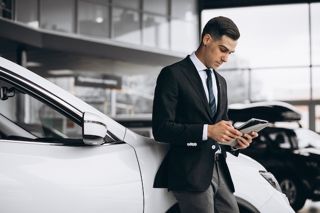 Young handsome man in car showroom Free Photo
