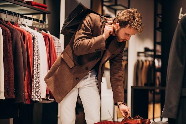 Young handsome man choosing cloth at shop Free Photo