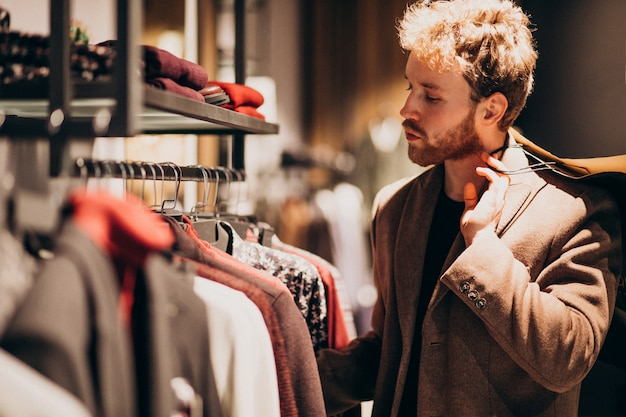 Young handsome man choosing cloth at shop Free Photo