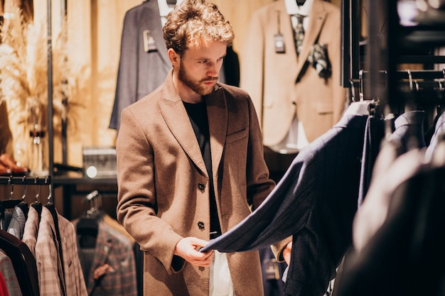 Young handsome man choosing clothes at shop Free Photo