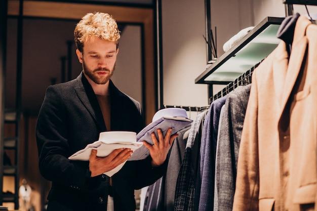 Young handsome man choosing shirt at a shop Free Photo