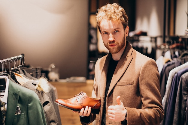 Young handsome man choosing shoes at a shop Free Photo