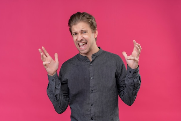 Giovane uomo bello pazzo e pazzo che grida e urla con espressione aggressiva Foto Gratuite
