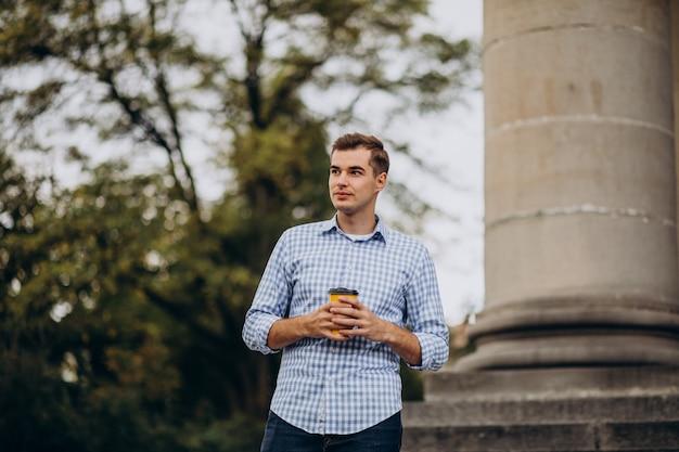 外でコーヒーを飲む若いハンサムな男 無料写真