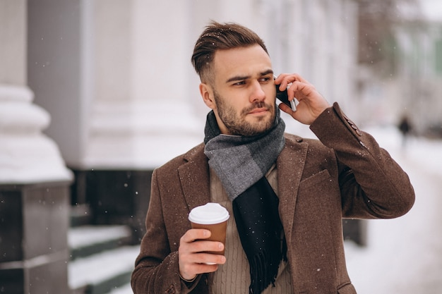 Young handsome man drinking coffee and talking on phone Free Photo