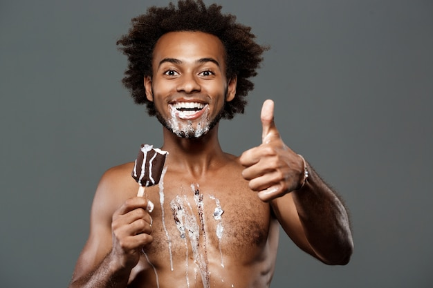 Молодой красавец ест мороженое на серую стену Бесплатные Фотографии