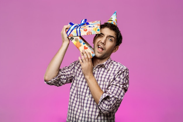 若いハンサムな男が紫色の壁を越えて誕生日ボックスから脱出します。 無料写真