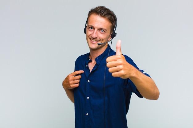 誇り、のんき、自信と幸せを感じ、親指を立てて前向きに笑う若いハンサムな男 Premium写真