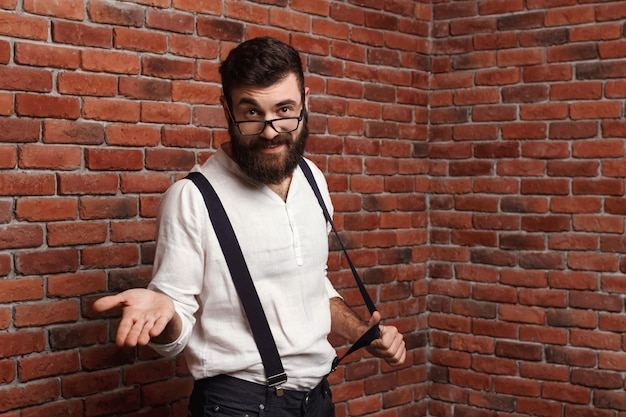 Young handsome man in glasses gesturing on brick wall. Free Photo