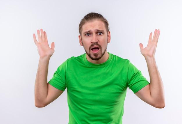 Giovane uomo bello in maglietta verde che guarda l'obbiettivo deluso con le braccia alzate in piedi su sfondo bianco Foto Gratuite