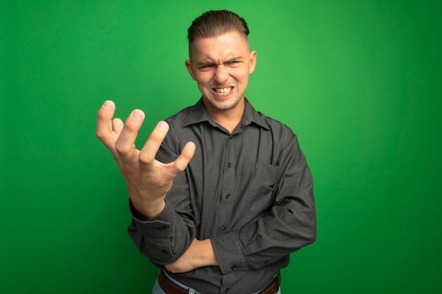 Giovane uomo bello in camicia grigia guardando la parte anteriore con il braccio fuori pazzo pazzo andando selvaggio in piedi sopra la parete verde Foto Gratuite