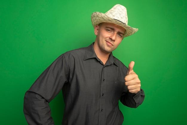 Giovane uomo bello in camicia grigia e cappello estivo guardando davanti, sorridente con la faccia felice e mostrando il pollice in alto in piedi sopra il muro verde Foto Gratuite