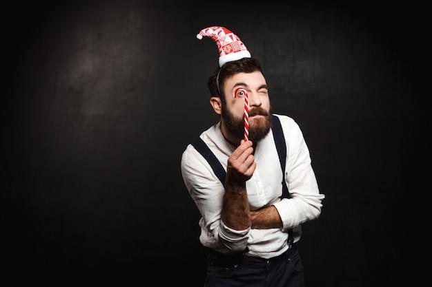 Молодой красивый человек держа конфету рождества над чернотой. Бесплатные Фотографии