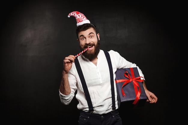 Молодой красивый человек, держащий рождественский подарок над черным. Бесплатные Фотографии