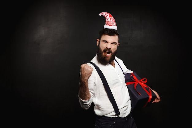 黒の上にクリスマスギフトボックスを置く若いハンサムな男。 無料写真