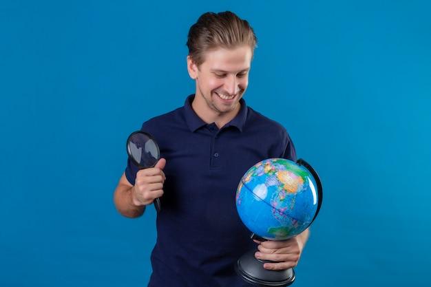 Молодой красивый мужчина держит глобус и увеличительное стекло, глядя на глобус, улыбаясь со счастливым лицом, стоящим на синем фоне Бесплатные Фотографии