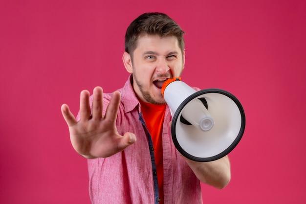 Молодой красивый мужчина держит мегафон, кричит ему, делая знак остановки рукой Бесплатные Фотографии