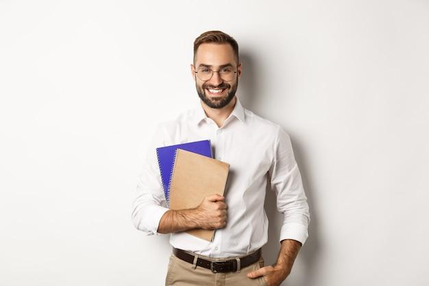 Giovane uomo bello che tiene i taccuini, concetto di e-learning e corsi. Foto Gratuite